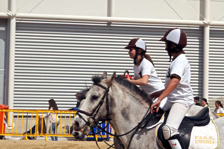Girls from Umbria region in their numbered uniforms riding their horse at Roma Cavalli 2011 event. Stock Photo - 9386507