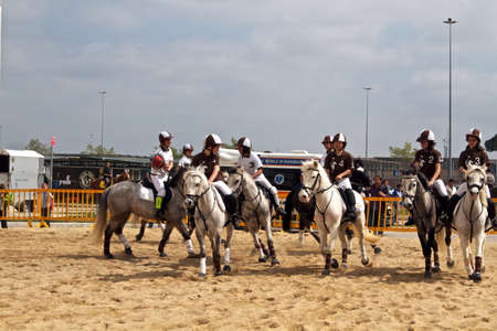 Girls from Umbria region in their numbered uniforms riding their horse at Roma Cavalli 2011 event.
