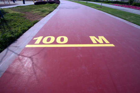 100 m mark on a public running track in a public park Stock Photo