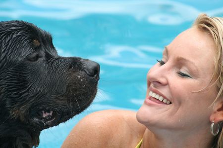 Woman swimming with rottweiler Imagens