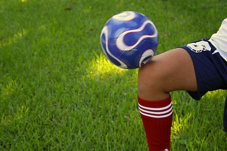 soccer bal on knee - closeup Stock Photo