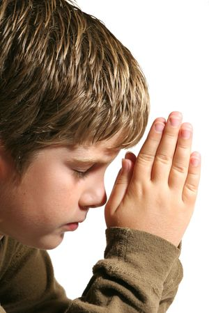 young boy praying with hands on white Imagens