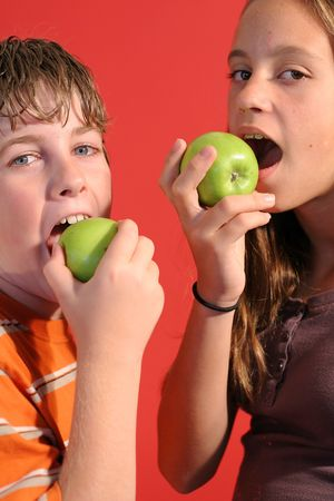 preteen  pure: boy & girl eating an apple vertical