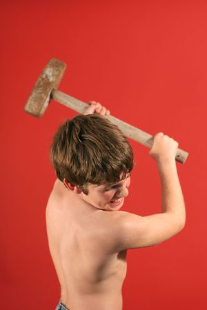pre adolescent boys: boy swinging sledge hammer vertical
