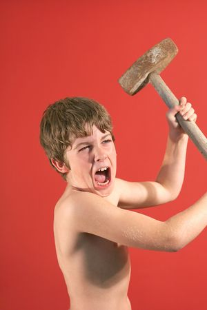 pre adolescent boys: angry boy swinging slede hammer vertical