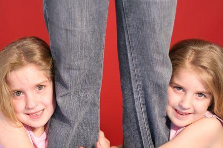 ni�as gemelas: muchachas gemelas que llevan a cabo las piernas de las madres Foto de archivo