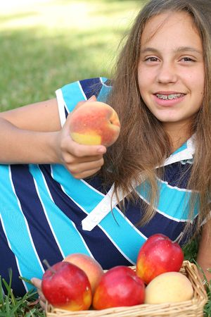 simple girl: girl with peaches & apples vertical Stock Photo