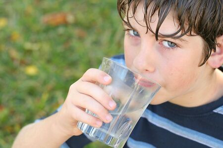 pre adolescents: boy drinking a glass of water