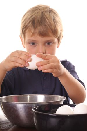 poach: little boy breaking an egg Stock Photo
