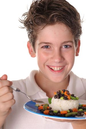 happy young boy eating healthy rice, beans & veggies vertical Imagens