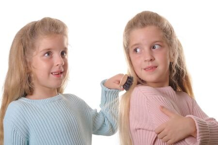fraternal: twin child brushing sisters hair