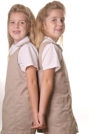 twin school girls vertical holding hands back photo