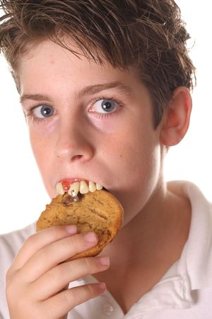 young boy with rotten teeth eating a cookie
