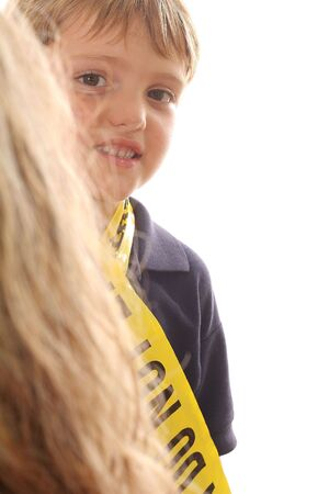 little boy peeking around a child photo