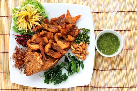 dinner food: A dish of fried fish with herbs on bamboo tray