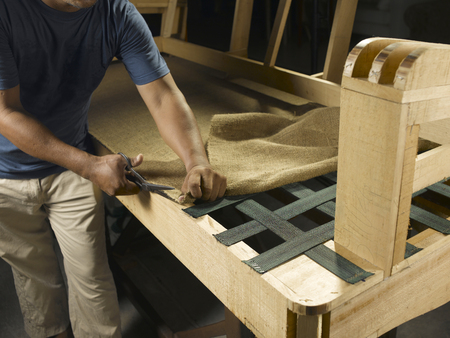 A craftsman is working to build the sofa.