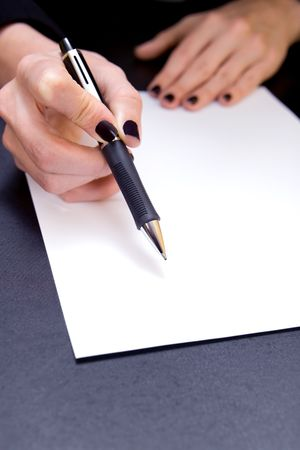 hand holding pen: Close-up of hand holding pen pointing to blank document
