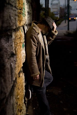 Man with hat covering his face