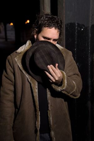 Man with hat covering his face in dark alley