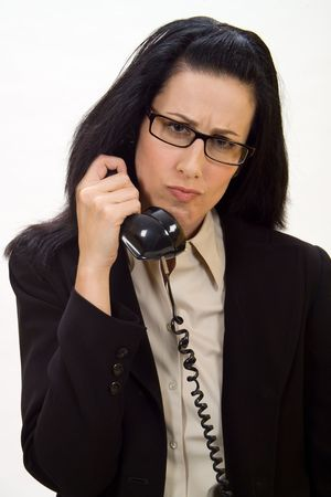 unsolicited: Woman holding an old school phone looking disturbed Stock Photo