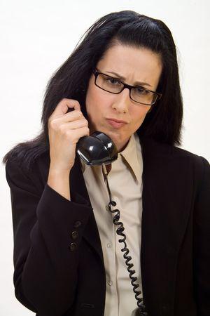 Woman holding an old school phone looking disturbed Banco de Imagens