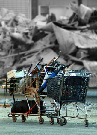 Shopping cart filled with recyclables in front of demolished building Stockfoto