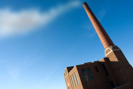 Old industrial factory with smokestack and sky