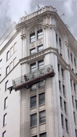 restoring: Construction workers in gondola restoring urban building facade
