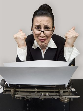 conservative: Retro business woman at vintage typewriter looking frustrated