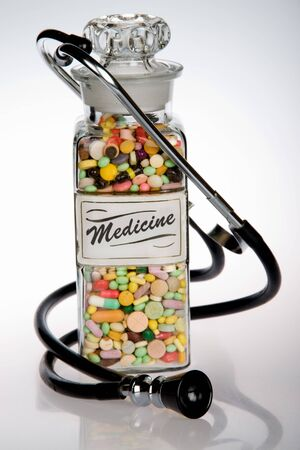 Retro medical concept featuring antique pill bottle and old stethoscope Stock Photo - 2047202