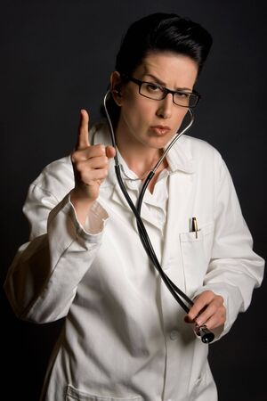 health care professional: Female health care professional with stern look raising finger