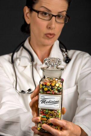 nursing bottle: Medical professional in white coat showing vintage medicine pill glass Stock Photo