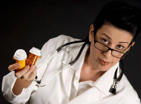 nursing bottle: Medical professional in white coat showing pill bottles