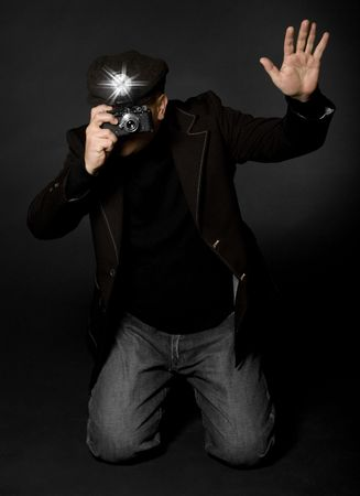 photography session: Retro style photographer with vintage camera and flash holding up his hand taking a picture Stock Photo