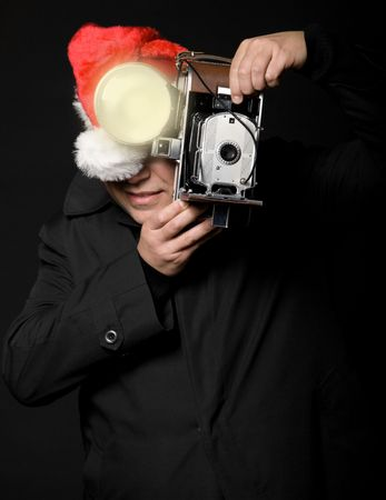 photography session: Photographer wearing santa hat taking a picture with vintage camera and flash Stock Photo