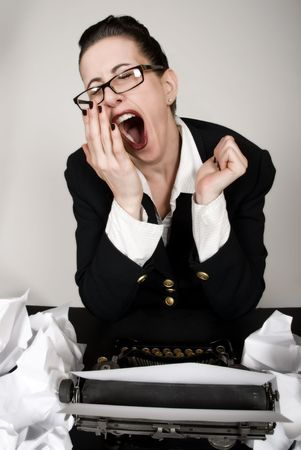 Retro business woman with vintage typewriter yawning photo