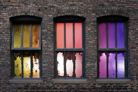urban decline: 3 old weathered windows with backlight during sunset