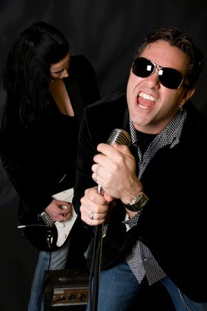 Male lead singer with retro mic and female guitar player in background photo