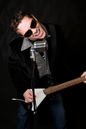 Male musician performing with guitar and retro mic Reklamní fotografie