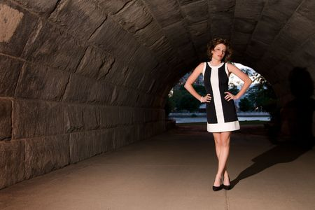 Beautiful young lady standing in underpass with city park in background Stock Photo - 3364265