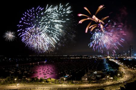 holiday lights display: Night time aerial view of downtown Chicago lakefront during independence day fireworks