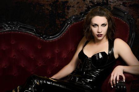 Mooie jonge vrouw in latex Catsuit over klassieke rode bank