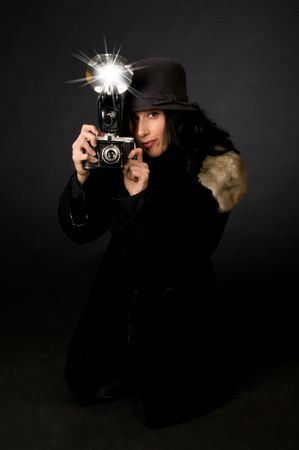 photography session: Retro style female photographer with vintage camera and flash Stock Photo