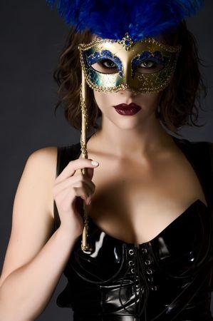 キャット スーツを着てカーニバル マスクを保持している美しい若い女性
