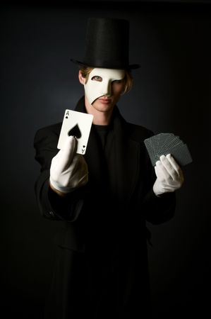 Young male magician playing with cards photo