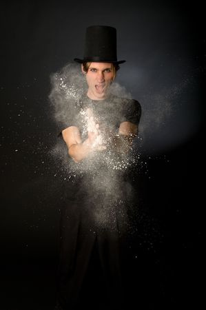 Young male magician playing with magic powder photo