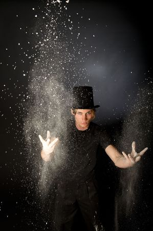 hocus pocus: Young male magician throwing magic powder Stock Photo