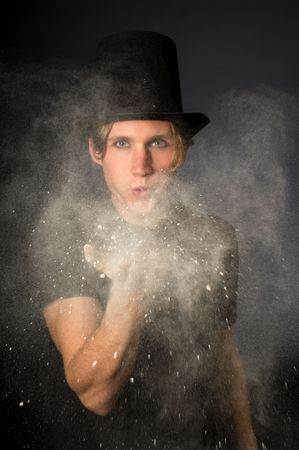Young male magician blowing magic powder