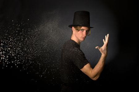Young male magician throwing magic powder photo