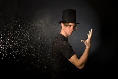 Young male magician throwing magic powder Stock Photo